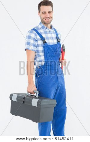 Portrait of smiling young male repairman carrying toolbox on white background