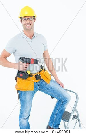 Portrait of confident worker holding drill machine on step ladder over white background
