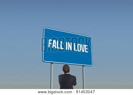 The word fall in love and thinking businessman against blue sky