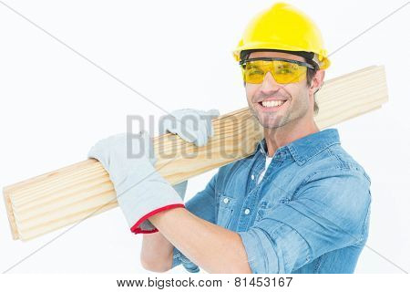 Portrait of happy carpenter wearing hardhat and protective glasses while carrying wooden planks over white background