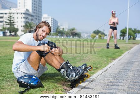 Fit man getting ready to roller blade on a sunny day