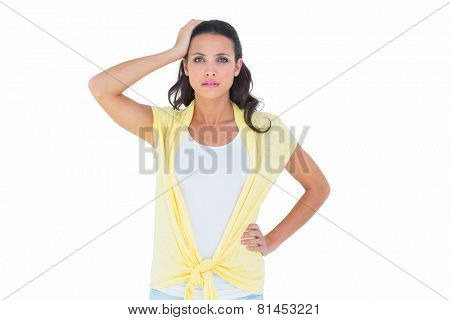 Confused brunette looking at camera on white background