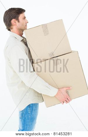 Side view of of delivery man carrying cardboard boxes on white background