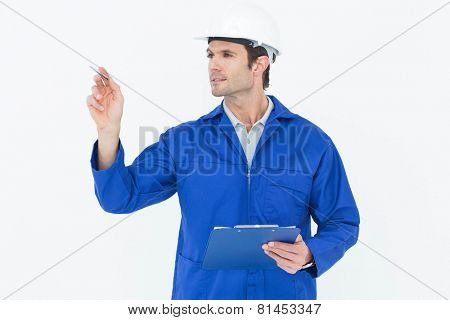 Handsome supervisor inspecting while holding clip board over white background