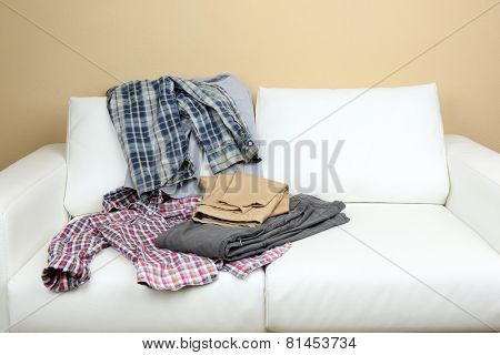 Messy clothing on white sofa, on  light wall background