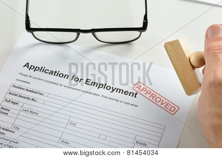 Hand With Rubber Stamp And Approved Employment Application