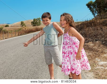 two children  hitchhiking along the street, portrait