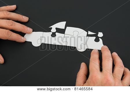 Person Solving Car Jigsaw Puzzle