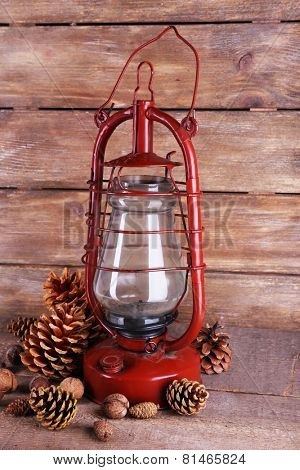 Kerosene lamp with cones ans walnuts on wooden planks background