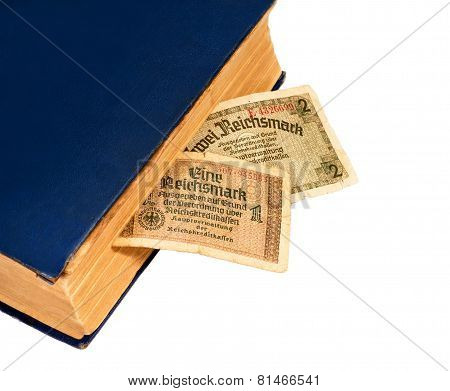 Reichsmarks Bill Of Germany And Old Book Isolated On White