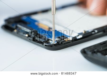 Human Hand Repairing Cellphone With Screwdriver
