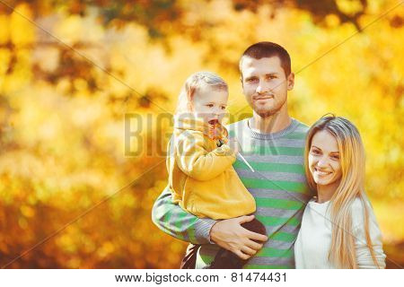 Young family on a walk in the autumn Park.