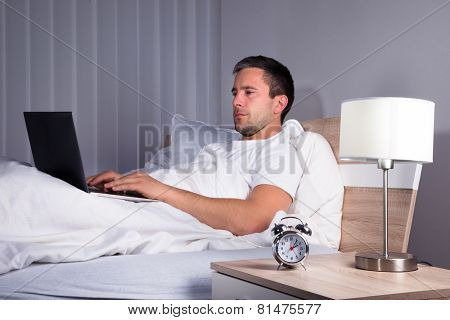 Man In Bedroom Using Laptop