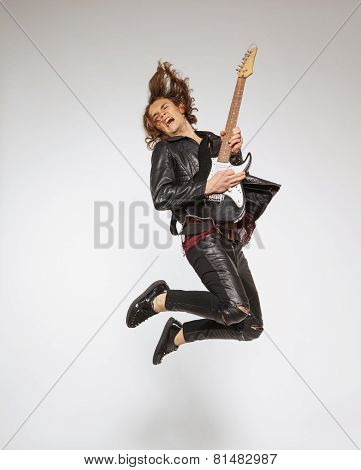 Young guitar player isolated on grey