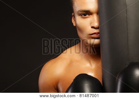 Handsome boxer posing with a punching bag on dark background