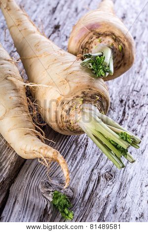 Fresh parsnip on old wooden table.