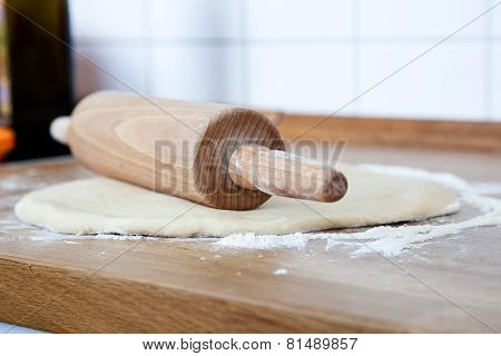 Rolling Pin On Pizza Dough In The Kitchen