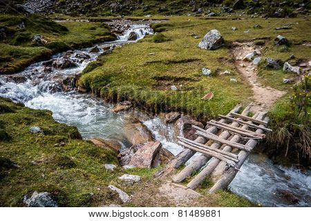 Wooden Bridge Across Running River In The Countryside