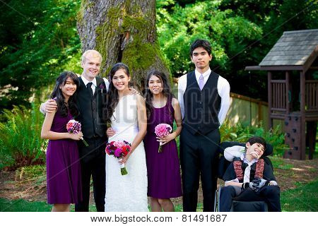 Interracial Wedding. Groom Standing With His Biracial Bride's Brothers And Sisters Outdoors. Younges