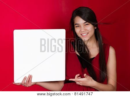 Beautiful Biracial Teen Girl Holding Up Square White Sign, Pointing To It On Red Background