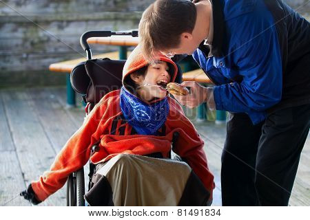 Father Feeding Disabled Son A Hamburger In Wheelchair. Child Has Cerebral Palsy
