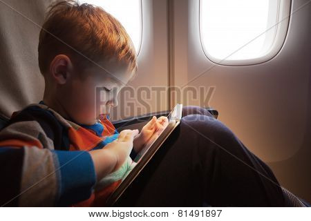 Child using tablet computer during flight