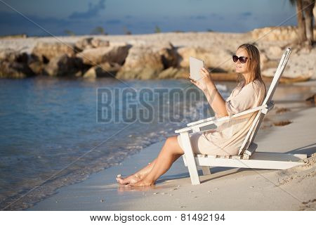 Woman with pad relaxing in chaise-lounge on the beach