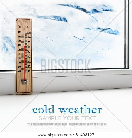 Thermometer On A Frozen Window And Cold Weather Outside