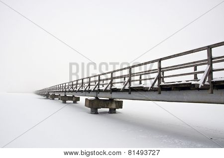 Old Long Wooden Bridge On Winter Lake Snowy Ice And Fog
