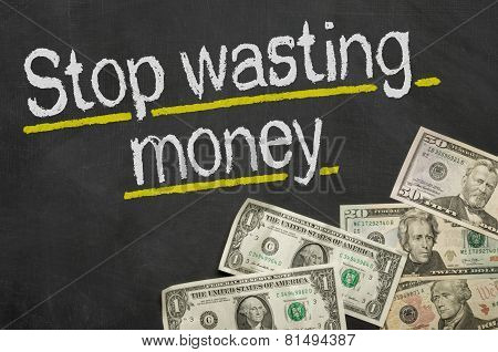 Text on blackboard with money - Stop wasting money