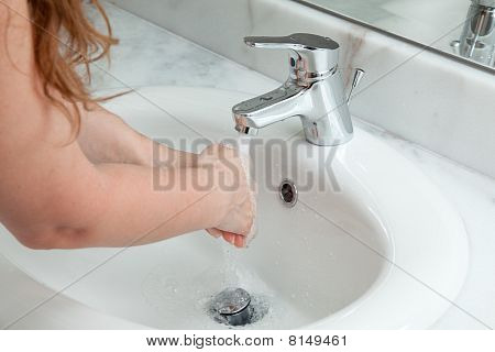 woman washing hands in bathroom