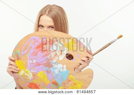 Young beautiful artist posing with a palette