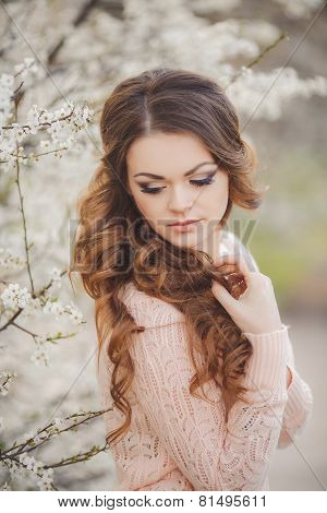 Portrait of a beautiful young woman in a spring garden.
