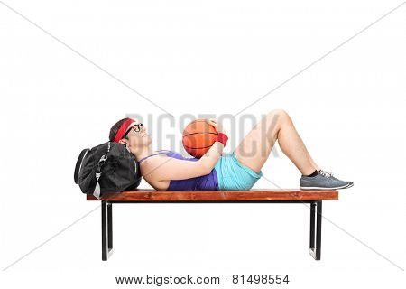Young man lying on a bench and holding basketball isolated on white background