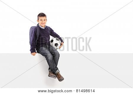 Schoolboy holding soccer ball seated on a panel isolated on white background
