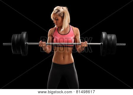 Attractive female athlete exercising with barbell on black background