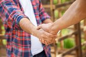 foto of crop  - Cropped image of construction workers shaking hands in cabin at site - JPG