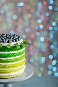 stock photo of sponge-cake  - Nice sponge happy birthday cake with mascarpone and grapes on the cake stand on festive light bokeh - JPG