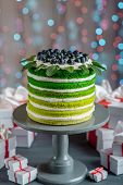 image of cake stand  - Nice sponge happy birthday cake with mascarpone and grapes with on the cake stand with gift boxes on festive light bokeh background - JPG
