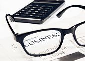 picture of newspaper  - business word see through glasses lens on financial newspaper near calculator business concept - JPG
