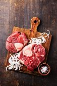 foto of beef shank  - Raw fresh cross cut veal shank and Ingredients for making Osso Buco on wooden cutting board on dark wooden background - JPG