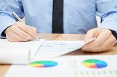 stock photo of financial audit  - Bussinessman examines data and numbers and finalizing report - JPG