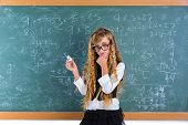 stock photo of clever  - Clever nerd pupil blond girl in green board thinking student schoolgirl - JPG
