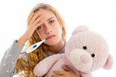 picture of pajamas  - blond girl with thermometer and flu cold in pajama  grumpy face with teddy bear - JPG