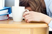 Dozy Woman Sleeping On Table In Office