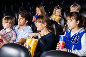 stock photo of watching movie  - Families having snacks while watching movie in cinema theater - JPG