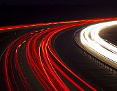 stock photo of lorries  - Cars and lorries leave ghostly light trails as they pass by quickly on this night road - JPG