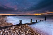 pic of shingles  - Waves break on a shingle beach overlooking the Isle of Wight - JPG