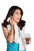 foto of biracial  - Beautiful biracial teenage girl drinking water while wiping off sweat - JPG
