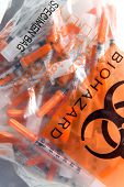 stock photo of hazard symbol  - Used Hypodermic needles in a Bio Hazard Bag - JPG